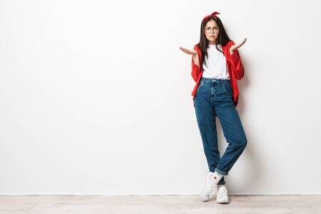 Full length portrait of a cute confused teenage girl wearing casual outfit standing isolated over white background, shrugging shoulders