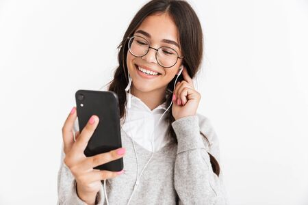 Attractive cheerful schoolgirl wearing unifrom standing isolated over white background, listening to music with earphones, holding mobile phone 스톡 콘텐츠