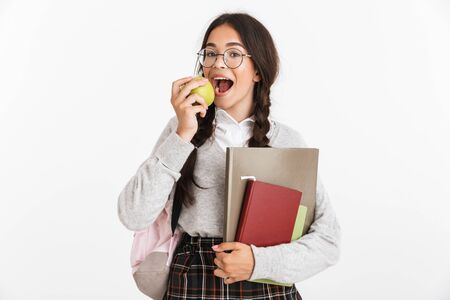 Photo closeup of lovely teenage girl wearing eyeglasses smiling and eating green apple while holding studying books isolated over white background