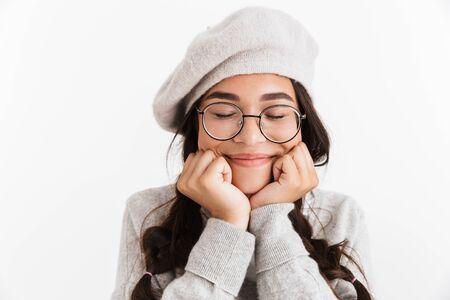 Atractiva colegiala feliz vistiendo unifrom que se encuentran aisladas sobre fondo blanco, los ojos cerrados