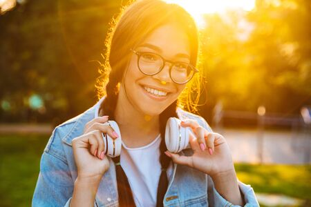 Image of a pleased happy young teenage girl student sitting outdoors in beautiful green park listening music with headphones. Stock Photo
