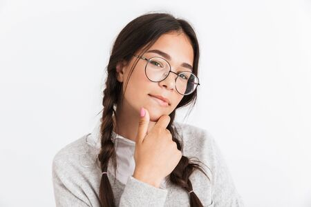 Photo closeup of thoughtful teenage girl wearing eyeglasses touching her chin and looking at camera isolated over white background Stock Photo