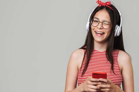 Cute cheerful teenage girl wearing casual outfit standing isolated over gray background, listening to music with headphones, using mobile phone, winking 스톡 콘텐츠