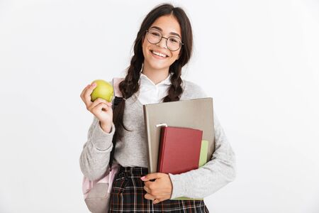 Photo closeup of caucasian teenage girl wearing eyeglasses smiling and eating green apple while holding studying books isolated over white background