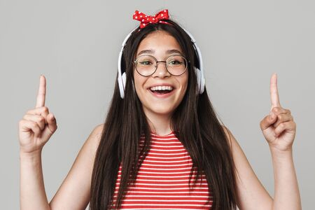 Cute happy teenage girl wearing casual outfit standing isolated over gray background, listening to music with headphones, pointig up