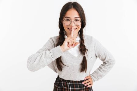 Photo closeup of lovely teenage girl wearing eyeglasses smiling while holding finger at her mouth isolated over white background Stock Photo