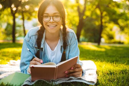Photo of a cheerful young student girl wearing eyeglasses sitting outdoors in nature park writing notes reading book. Looking camera. 스톡 콘텐츠