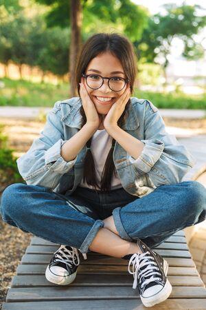 Foto di una giovane studentessa carina felice e contenta che indossa occhiali seduta su una panchina all'aperto nel parco naturale.