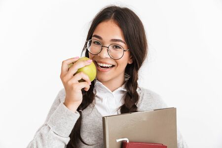Photo closeup of joyful teenage girl wearing eyeglasses smiling and eating green apple while holding studying books isolated over white background Stock Photo