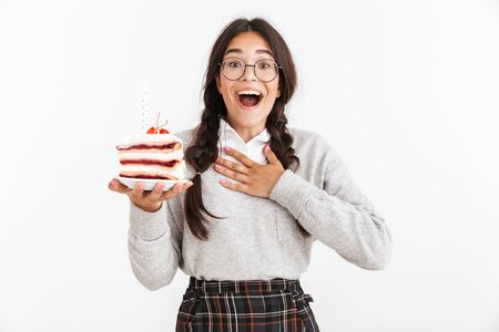 Photo closeup of delighted teenage girl wearing eyeglasses smiling while holding big slice of birthday cake isolated over white background Stock Photo