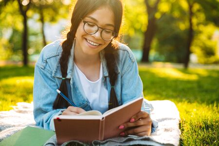 Portrait of a smiling young student girl wearing eyeglasses sitting outdoors in nature park writing notes reading book.