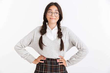 Photo closeup of cheerful teenage girl wearing eyeglasses and school uniform smiling at camera isolated over white background