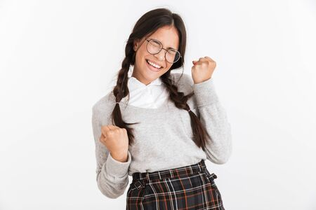 Photo closeup of adorable teenage girl wearing eyeglasses and school uniform rejoicing with clenching fists isolated over white background