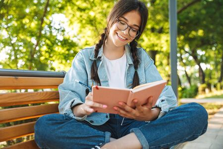 Photo of a pleased cheerful cute young student girl wearing eyeglasses sitting on bench outdoors in nature park writing notes in notebook. 스톡 콘텐츠