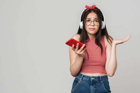 Cute teenage upset confused girl wearing casual outfit standing isolated over gray background, listening to music with headphones, using mobile phone 스톡 콘텐츠