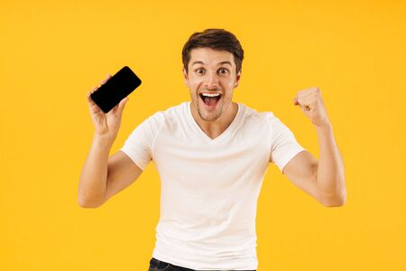 Image of a happy excited shocked young man in casual white t-shirt using mobile phone isolated over yellow background make winner gesture. Stock Photo