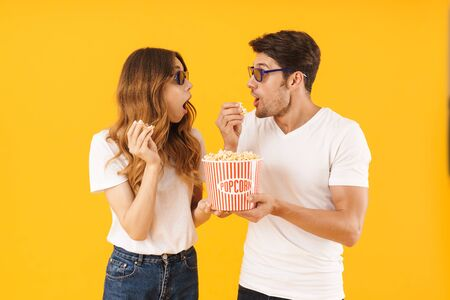 Portrait of surprised couple man and woman in 3D glasses rejoicing while standing together with popcorn bucket isolated over yellow background