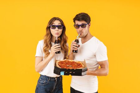 Portrait of happy couple man and woman in 3D glasses drinking soda beverage and holding pizza boxes isolated over yellow background