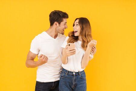 Portrait of pleased couple man and woman in basic t-shirts looking at each other while holding smartphone isolated over yellow background