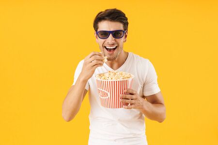 Image of a laughing happy young man in casual white t-shirt eat popcorn wearing 3d glasses watch film isolated over yellow background.
