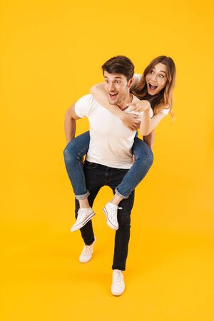 Full length portrait of joyful couple man and woman in basic t-shirts looking at copyspace together while doing piggyback ride isolated over yellow background