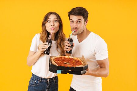 Portrait of joyful couple man and woman in basic t-shirts drinking soda beverage and holding pizza boxes isolated over yellow background Stock Photo