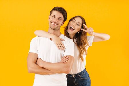 Portrait of joyous couple in basic t-shirts standing together while woman hugging man and showing peace sign at camera isolated over yellow background