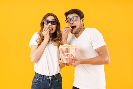 Portrait of shocked couple man and woman in 3D glasses being scared while standing together with popcorn bucket isolated over yellow background
