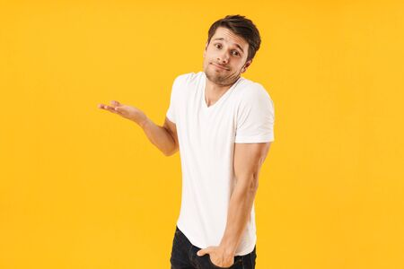 Photo of young man in basic t-shirt looking at camera and throwing up arm isolated over yellow background Stock Photo