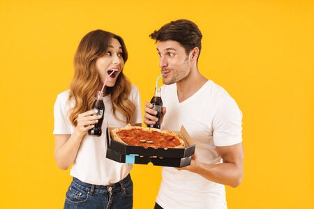 Portrait of young couple man and woman in basic t-shirts drinking soda beverage and holding pizza boxes isolated over yellow background