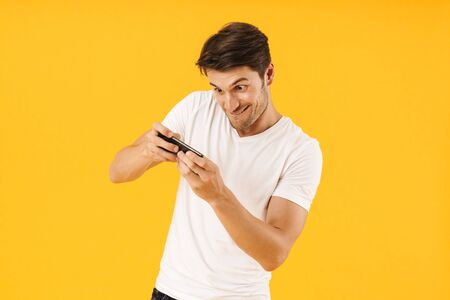 Image of emotional nervous young man in casual white t-shirt play games by mobile phone isolated over yellow background.