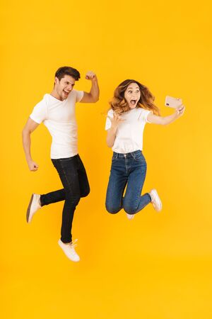 Full length portrait of happy couple man and woman in basic t-shirts laughing at camera while taking selfie photo isolated over yellow background