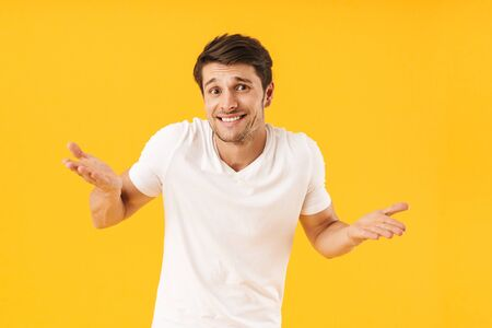 Photo of handsome man in basic t-shirt smiling at camera and throwing up arms isolated over yellow background Stock Photo