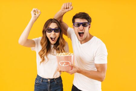 Portrait of pleased couple man and woman in 3D glasses rejoicing while standing together with popcorn bucket isolated over yellow background Stock Photo