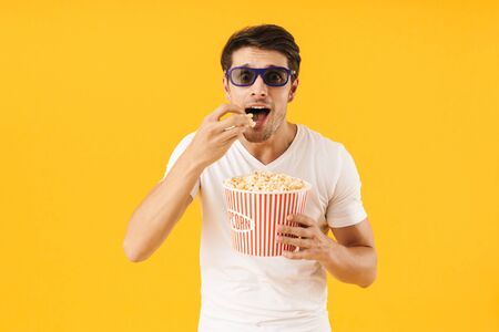 Photo of a concentrated young man in casual white t-shirt eat popcorn wearing 3d glasses watch film isolated over yellow background.