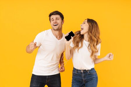 Portrait of delighted couple man and woman in basic t-shirts singing while using smartphone and earphones together isolated over yellow background