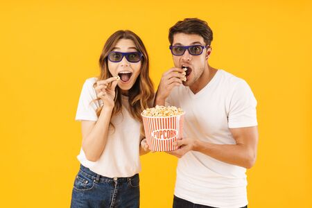 Portrait of excited couple man and woman in 3D glasses rejoicing while standing together with popcorn bucket isolated over yellow background