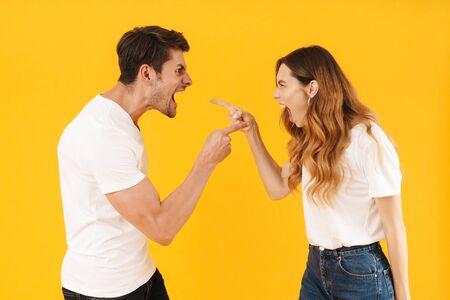 Foto de la pareja enojada ofendida hombre y mujer en camisetas básicas gritando el uno al otro mientras está de pie frente a frente aislado sobre fondo amarillo
