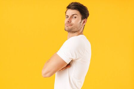 Photo of serious man in basic t-shirt frowning and looking at camera with arms crossed isolated over yellow background