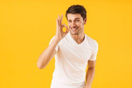 Foto van een gelukkige man in een basic t-shirt die naar de camera glimlacht terwijl hij een ok-teken toont dat op een gele achtergrond wordt geïsoleerd Stockfoto