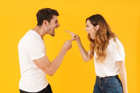 Photo of irritated aggressive couple man and woman in basic t-shirts screaming at each other while standing face to face isolated over yellow background