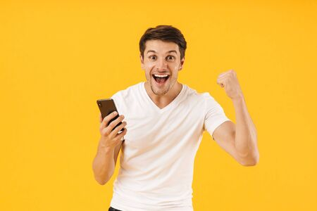 Das Bild eines schreienden, glücklichen, schockierten jungen Mannes in einem lässigen weißen T-Shirt mit einem Mobiltelefon, das auf gelbem Hintergrund isoliert ist, macht Siegergeste.