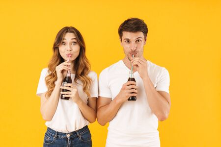 Portrait of beautiful couple man and woman in basic t-shirts standing together while drinking soda beverage with straws isolated over yellow background