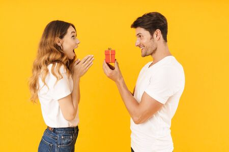 Portrait of excited couple standing together while handsome man making proposal to happy woman with ring box isolated over yellow background