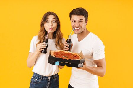 Portrait of happy couple man and woman in basic t-shirts drinking soda beverage and holding pizza boxes isolated over yellow background