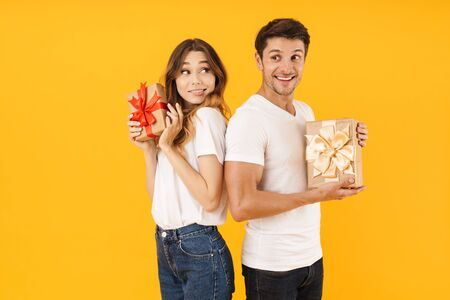 Portrait of pleased couple man and woman in basic t-shirts standing together while holding present boxes isolated over yellow background