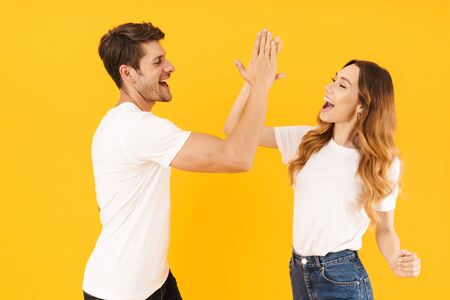 Portrait of caucasian couple man and woman in basic t-shirts rejoicing while giving high five together isolated over yellow background 版權商用圖片