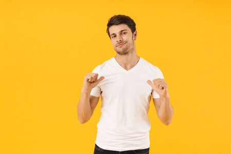 Photo of attractive man in basic t-shirt looking at camera and gesturing fingers at himself isolated over yellow background