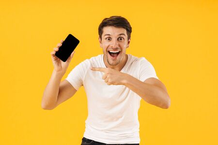 Image of a surprised young man in casual white t-shirt using mobile phone isolated over yellow background pointing to empty display.