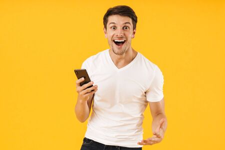 Image of a cheerful excited surprised young man in casual white t-shirt using mobile phone isolated over yellow background.